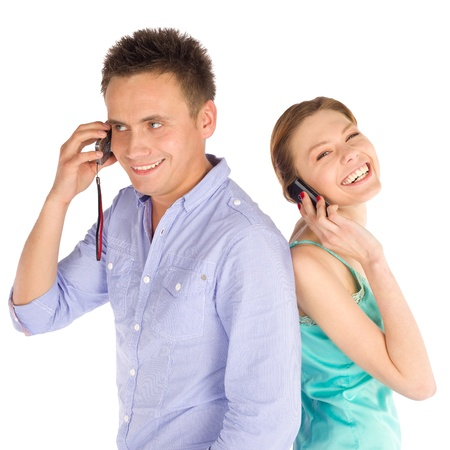 Young happy smiling couple standing back to back, talking on the phone, isolated on white background Stock Photo - 8784775