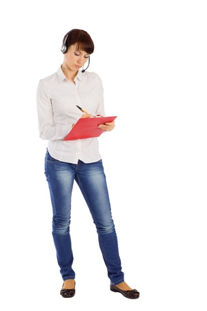 blank center: Young attractive female customer service representative with headset writing on clipboard, standing on isolated white background