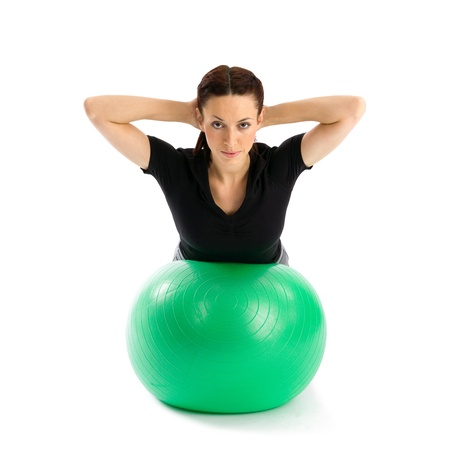 Pretty woman with hands behind head doing a pilates exercise using gym ball, isolated over a white background photo
