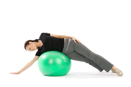 Pretty young fit woman practice with a pilates ball, isolated over a white background