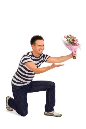 Gut aussehend casual junger Mann Übergabe Nelken Blumen am Valentinstag, isolated on white background