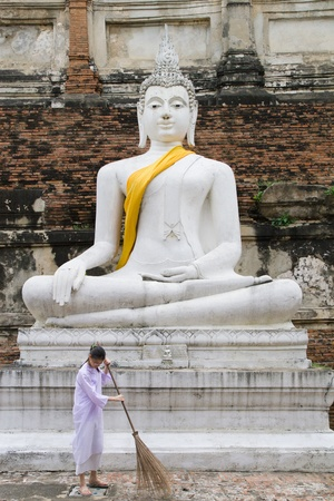 charlady: AYUTTHAYA, THAILAND - OCTOBER 16: Cleaning lady in front of Buddha statue in the Wat Yai Chai Mongkol complex on October 16, 2007 in Ayutthaya, Thailand Editorial