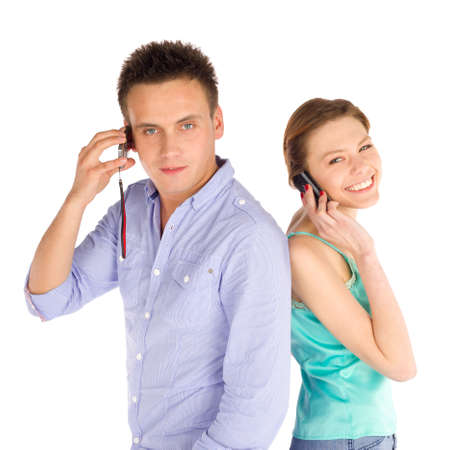 Young happy casual students standing back to back, talking on the phone, isolated on white background Stock Photo - 9000375