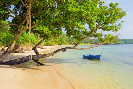 Scenic remote white sand beach on the tropical island in Thailand, small boat and swing attached to a tree photo