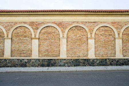 Classic decorative brick wall with columns, arches and stone base next to the sidewalk and street Stock Photo