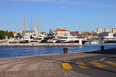 Luxury motor yachts docked at scenic harbor in Zadar, Croatia photo