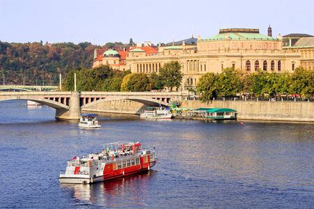 Prague scenery, passenger boats on Vltava river and Neo-Renaissance architecture of the Rudolfinum Concert Hall in Prague, Czech Republic