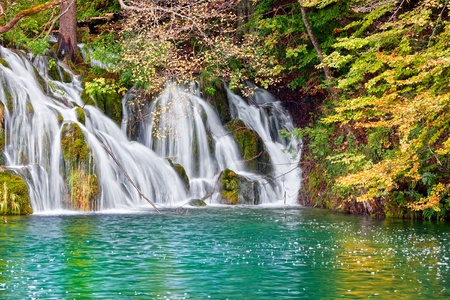Scenic autumn waterfall and small lake in the forest Stok Fotoğraf