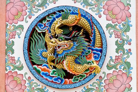 chinese wall: Oriental design of an ancient Chinese dragon on a temple wall in Thailand Stock Photo