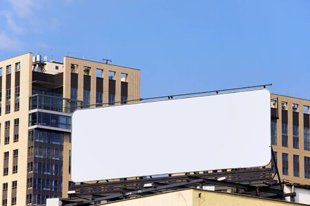 Large blank billboard on a building roof in the city downtown