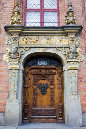 richly: Richly decorated antique door on a historic apartment house with marine motifs, crest and emblem of Poland and Gdansk in the Old Town of Gdansk (Danzig), Poland