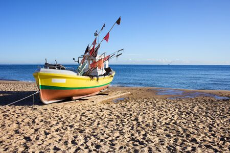 Single boat on a sandy beach at the Baltic Sea in Poland photo