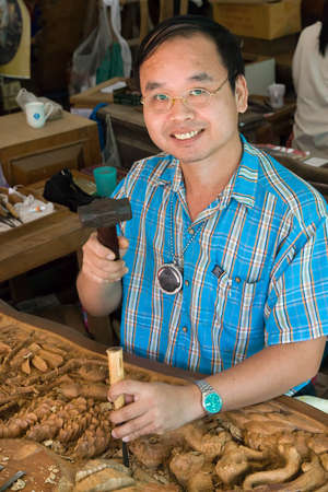 BANGKOK PROVINCE, THAILAND - NOVEMBER 3: Professional sculptor at work in wood carving factory near Bangkok in Thailand on November 3, 2007