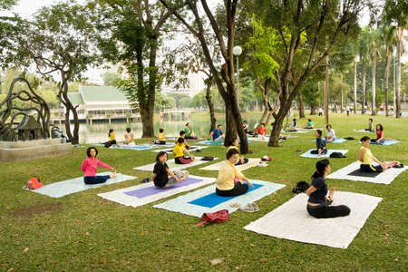 LUMPINI PARK, BANGKOK - DECEMBER 10: Group of people practising yoga on the grass in the Lumpini Park in Bangkok, Thailand on December 10, 2007