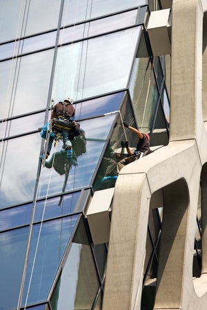 cleaning window: Man cleaning windows of a modern office building
