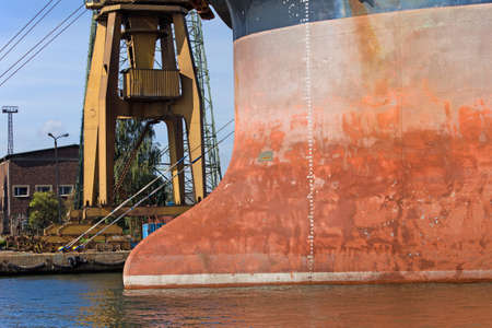 shiprepair: Shipyard industrial scenery, bow of a large cargo ship docked at waterfront