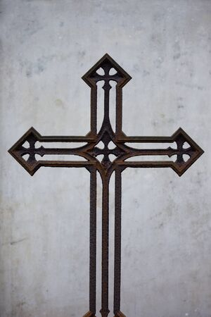 Interesting old 19th century vintage rusty metal cross with four other crosses integrated within the design, simple ascetic composition on conrete background photo