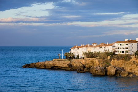 Morning at scenic coastline of the Mediterranean Sea with apartment houses on a rocky shore in Nerja town at the Costa del Sol, Andalusia region, Spain photo