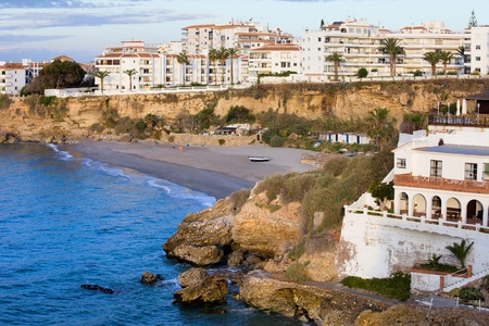Small tranquil beach surrounded by cliffs and apartment buildings in scenic resort town of Nerja at Costa del Sol, Andalucia, southern Spain photo
