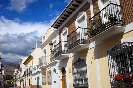 Scenic traditional apartment houses residential architecture on cosy tranquil street in resort town of Nerja, Andalusia region, southern Spain photo