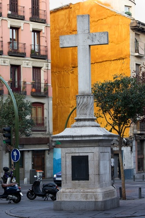 Stone cross made in 1738 against a vivid orange wall at the Plaza de Puerta Cerrada in the old part of Madrid in Spain photo