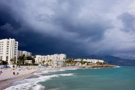 Apartment houses along Costa del Sol sandy beach in resort town of Nerja at the Mediterranean Sea in southern Spain with dark cloudy sky of a coming storm Stock Photo - 13591939