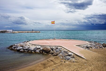 heliport: Heliport on the Mediterranean Sea with Spanish flag in Marbella, Costa del Sol, Malaga Province, Spain Stock Photo