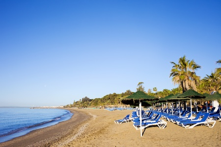 Sun loungers on a sandy beach by the Mediterranean Sea at the popular resort of Marbella in Spain, Costa del Sol, Andalusia region, Malaga province photo