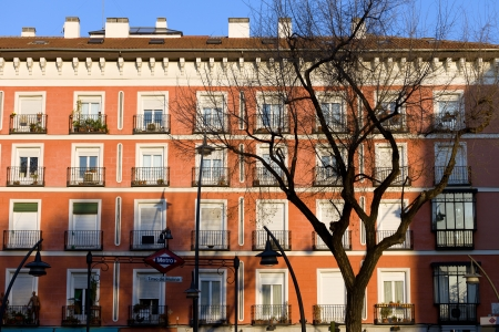tenement: Historic tenement house facade architecture at the Plaza Tirso de Molina in Madrid, Spain.