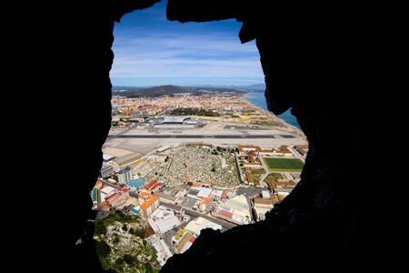 tunnel view: View through a hole in the Gibraltar Rock tunnel on the Gibraltar cemetery, airport runway and La Linea town at the far end.