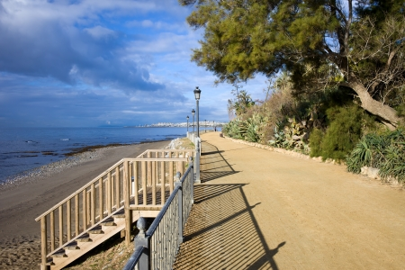 footway: Tranquil footpath with stairs to the beach by the Mediterranean Sea between Marbella and Puerto Banus (on the horizon) in Andalucia region, southern Spain.