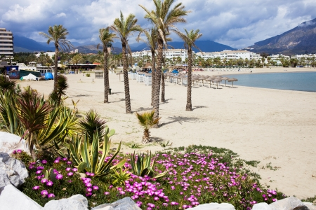 Sandy beach in resort town of Puerto Banus (near Marbella) on scenic Costa del Sol, Andalusia, Spain.