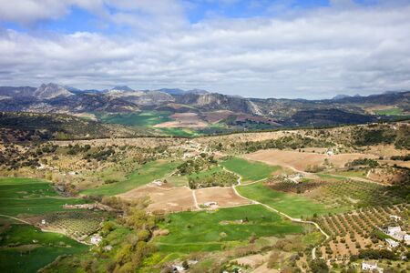 spanish landscapes: Picturesque landscape with cultivated fields and green meadows of hilly Andalusia countryside in southern Spain.