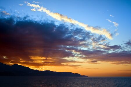 Last rays of sunlight shining through clouds over the sea at sunset on Costa del Sol in Spain. photo