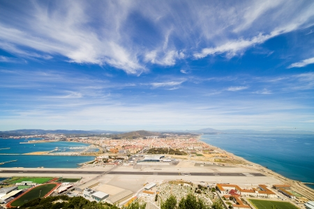 Gibraltar airport runway, La Linea de la Concepcion town in Spain at the far end, Mediterranean Sea on the right, Gibraltar Bay on the left and sky as a copyspace above.