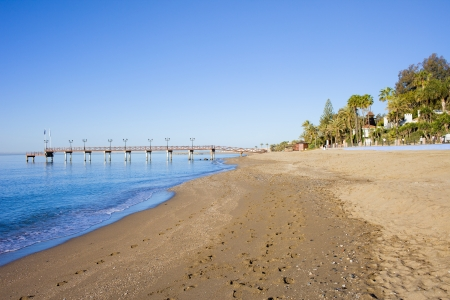 Beach and pier on Costa del Sol between resort town of Marbella and Puerto Banus in Spain, Malaga province  Stock Photo