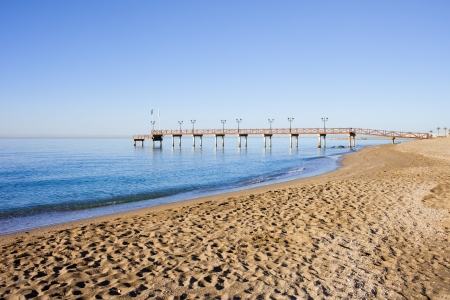 Tranquil scenery of a sandy beach and a wooden pier on Costa del Sol between resort town of Marbella and Puerto Banus in Spain, Malaga province photo