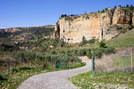 Paved road through the Andalusia countryside and rock of Ronda in Southern Spain, Malaga province  photo