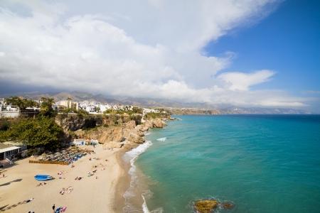 Summer holiday on Costa del Sol in Spain, sandy beach by the Mediterranean Sea in Nerja resort town. photo