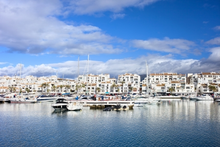 Marina waterfront with luxury motor yachts in holiday resort town of Puerto Banus on Costa del Sol, near Marbella in Spain, Malaga province.
