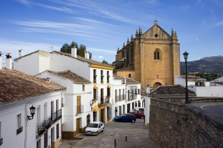 Houses on a picturesque street in the medieval old town of Ronda leading to the Church of the Holy Spirit, located in Spain, Andalusia region. photo