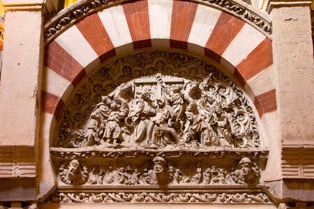 depicts: Religious carving framed by the Moorish Arabic arch, depicts the removal of Jesus Christ from the cross in Mezquita Cathedral, Andalusia, Spain