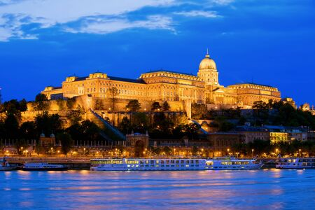 Buda Castle by the Danube river, illuminated at dusk in Budapest, Hungary
