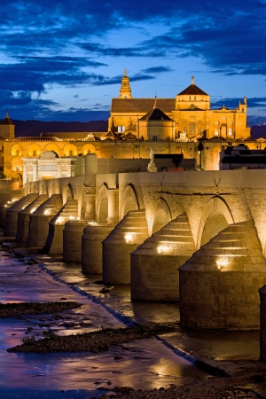 Roman Bridge on Guadalquivir river and The Great Mosque (Mezquita Cathedral) at twilight in the city of Cordoba, Andalusia, Spain.