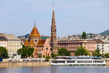 tenement: 19th century Buda Reformed Church, tenement houses and Danube River waterfront in Budapest, Hungary.