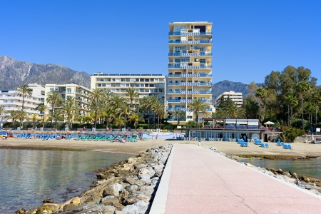 Pier, beach and apartment buildings in resort town of Marbella on Costa del Sol in Spain, Andalusia, Malaga province. photo