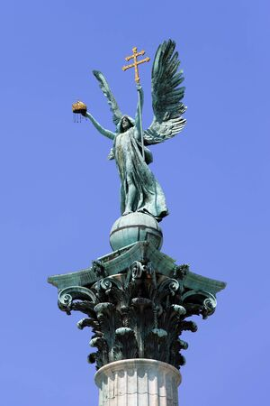 Archangel Gabriel statue holding Holy Crown of St. Stephen and Apostolic Cross, part of the Millennium Monument on the Heroes Square in Budapest, Hungary. photo
