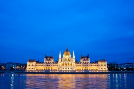 Budapest Parliament building in Hungary at dusk, reflections on the Danube river waters. photo