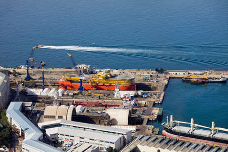 shiprepair: View from the Rock of Gibraltar on shipyard docks built in late 19th century, warehouses and Gibraltar Bay.