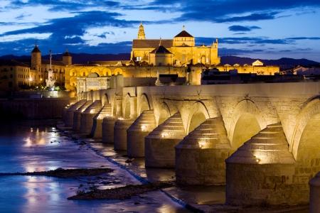 cordoba: Roman Bridge on Guadalquivir river and Mosque Cathedral (La Mezquita) illuminated at dusk in the city of Cordoba, Andalusia, Spain.